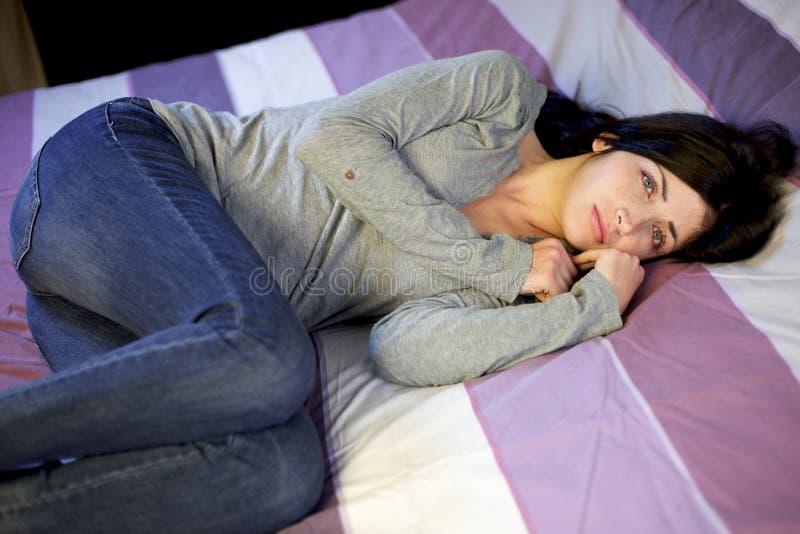 Droevige eenzame mooie vrouw in bed met familieprobleem royalty-vrije stock afbeelding