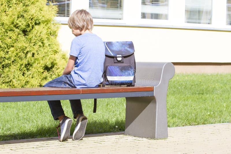 Droevige, eenzame, ongelukkige, teleurgestelde jongen het zitten alleen dichtbijgelegen school rugzak De achterinzameling van men stock afbeeldingen