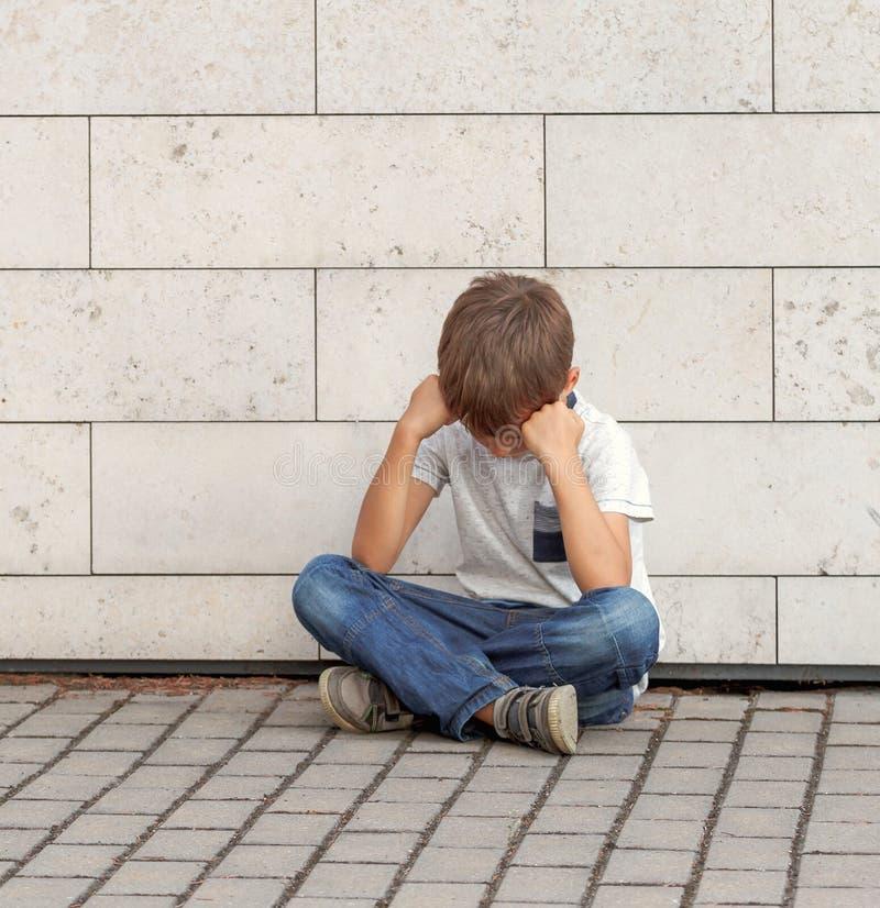 Droevige, eenzame, ongelukkige, teleurgestelde kindzitting alleen op de grond De jongen die zijn hoofd houden, kijkt neer openluc royalty-vrije stock afbeeldingen