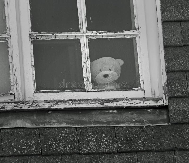 Droevige eenzame teddy bij venster royalty-vrije stock fotografie
