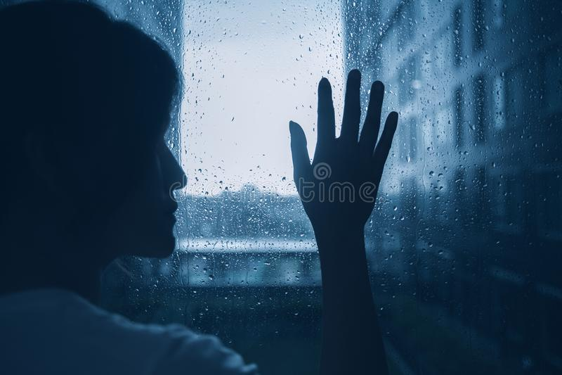 Droevige eenzame van het de vrouwensilhouet van de depressiestemming van het de aanrakingsglas de vensters regenachtige dag royalty-vrije stock afbeeldingen