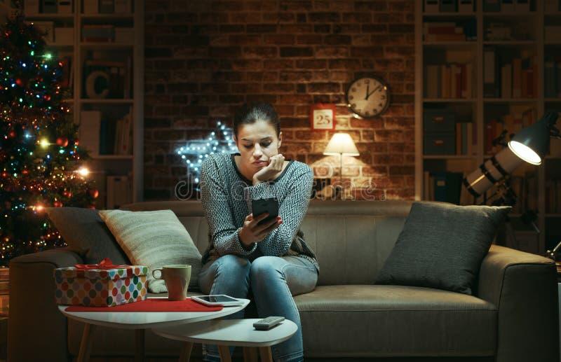 Droevige eenzame vrouw die op Kerstavond babbelen stock afbeelding