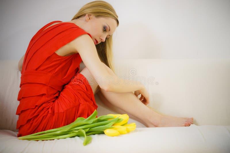Droevige elegante vrouwenzitting op bank met tulp stock afbeeldingen