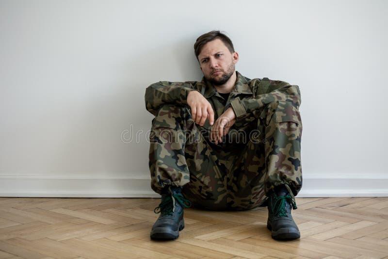 Droevige en eenzame militair in groene eenvormig met depressie en oorlogssyndroom royalty-vrije stock afbeelding