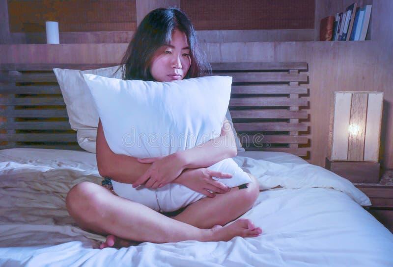 Droevige en gedeprimeerde Aziatische Koreaanse vrouw in bed die depressie aan bezorgdheid en slapeloosheid lijden die miserabel v stock foto
