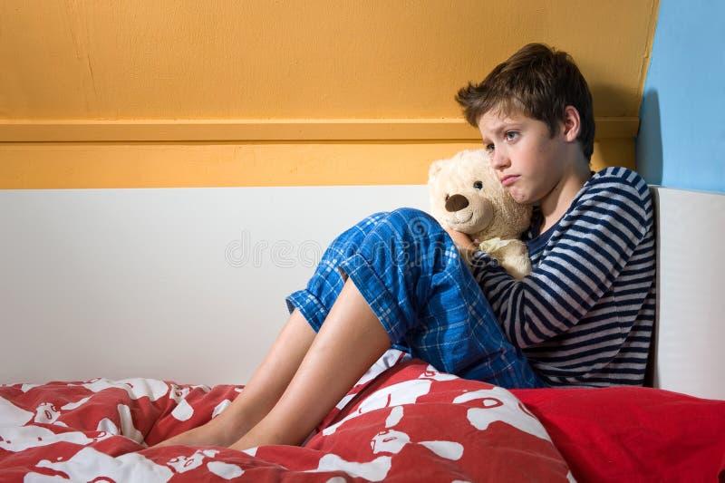 Droevige en gedeprimeerde jongen op zijn bed stock afbeeldingen