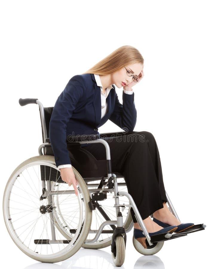 Droevige, ernstige bedrijfsvrouwenzitting op rolstoel. royalty-vrije stock foto