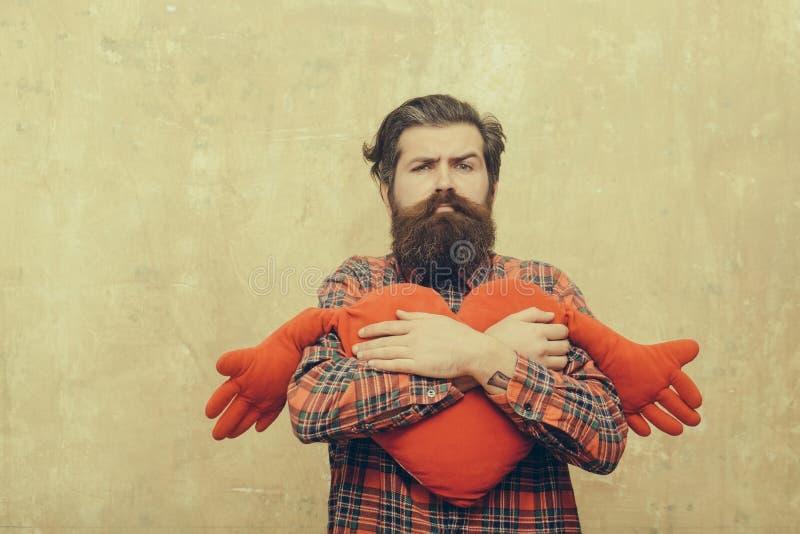 Droevige gebaarde mens die het rode stuk speelgoed van de hartvorm met handen koesteren royalty-vrije stock foto's