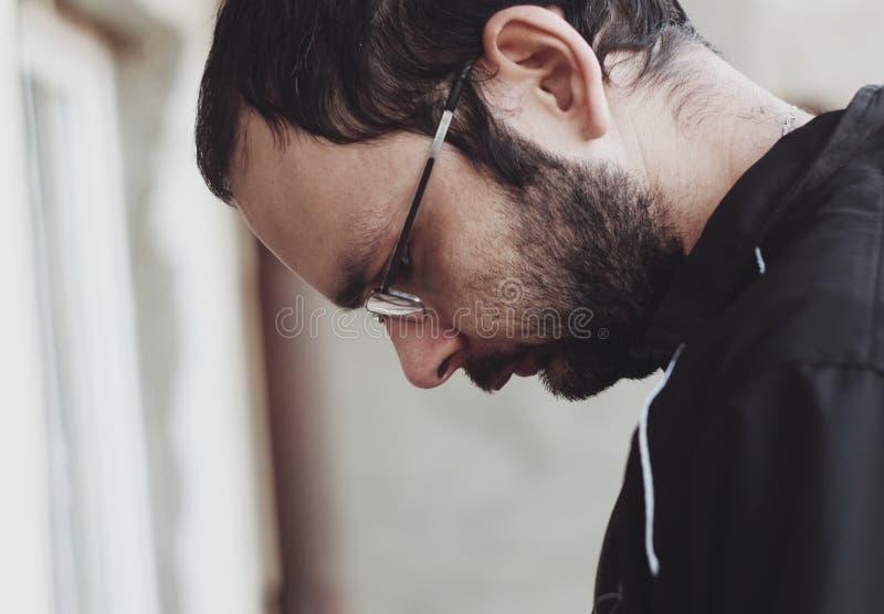 Droevige gebaarde mens met glazenportret stock foto