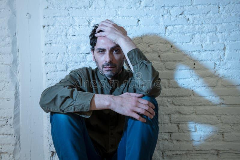 Droevige gedeprimeerde mens die tegen een muur in geestelijk gezondheidsconcept leunen royalty-vrije stock afbeeldingen
