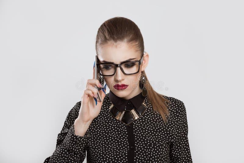 Droevige gedeprimeerde vrouw die op de telefoon spreken stock foto