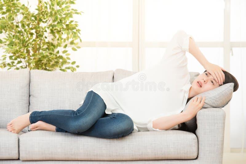 Droevige gedeprimeerde vrouw die thuis op de laag zitten stock afbeeldingen