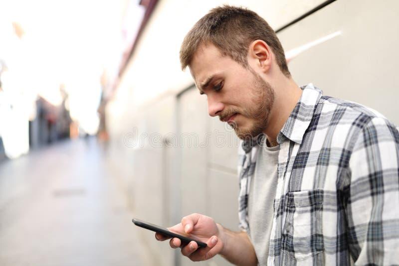 Droevige gewone man die een smartphone met behulp van royalty-vrije stock afbeelding