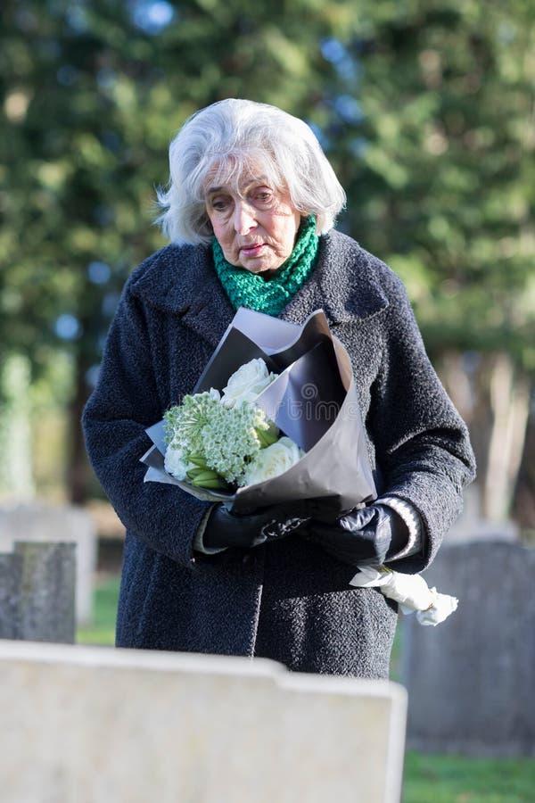 Droevige Hogere Vrouw met Bloemen die zich door Graf bevinden royalty-vrije stock afbeelding