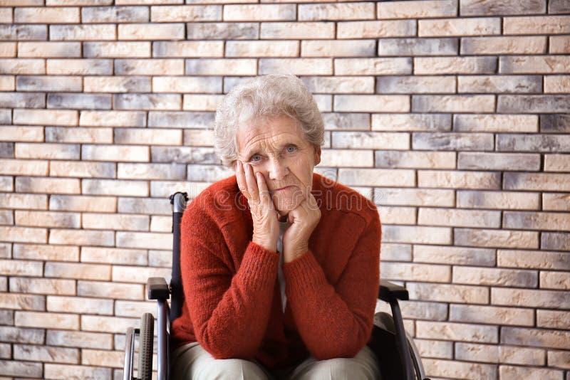 Droevige hogere vrouw in rolstoel tegen bakstenen muur royalty-vrije stock fotografie