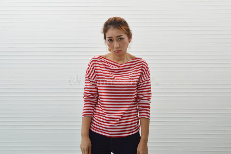 Droevige jonge Aziatische vrouw rood en wit gestript overhemd dragen en jeans die zich over muurachtergrond bevinden, Gefrustreer royalty-vrije stock afbeelding