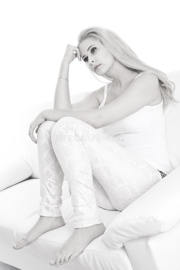 Droevige jonge blondevrouw die op wit wordt geïsoleerd royalty-vrije stock foto's