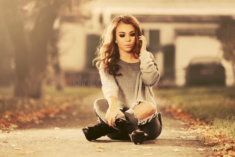 Droevige jonge maniervrouw die in gescheurde jeans op stoep zitten stock afbeelding