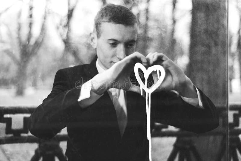Droevige jonge mens in liefde De kerel wordt bedroeft bekijkt het geschilderde hart op het venster Concept gebroken gevoel en royalty-vrije stock foto