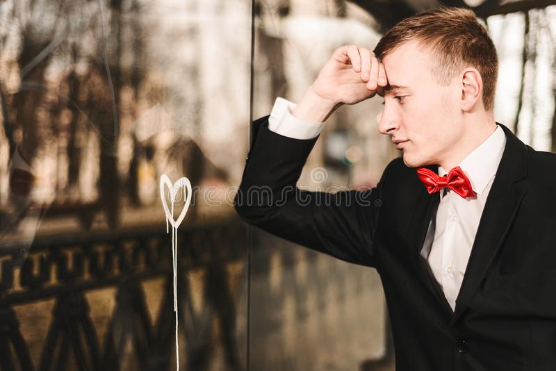 Droevige jonge mens in liefde De kerel wordt bedroeft bekijkt het geschilderde hart op het venster Concept gebroken gevoel en stock foto