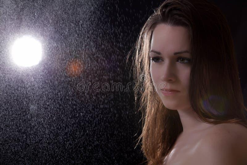 Droevige jonge vrouw in de regen stock foto