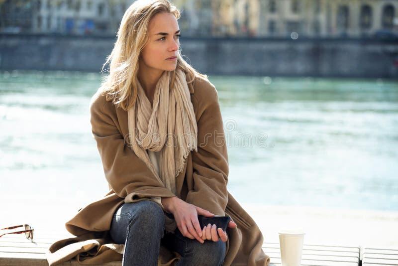 Droevige jonge vrouw die over haar problemen denken terwijl het zitten naast de rivier in de stad royalty-vrije stock foto
