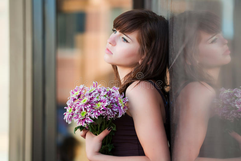 Droevige jonge vrouw met chrysant. stock fotografie