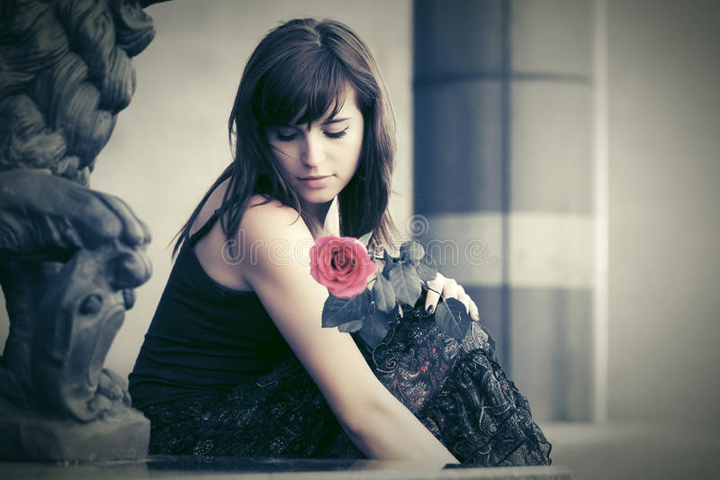 Droevige jonge vrouw met een rode roze zitting op grafsteen royalty-vrije stock afbeeldingen