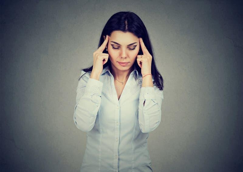 Droevige jonge vrouw met ongerust gemaakte beklemtoonde gezichtsuitdrukking die hoofdpijn hebben royalty-vrije stock afbeelding