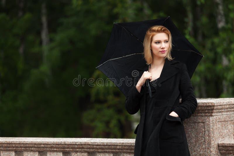 Droevige jonge vrouw met paraplu in de regen stock foto