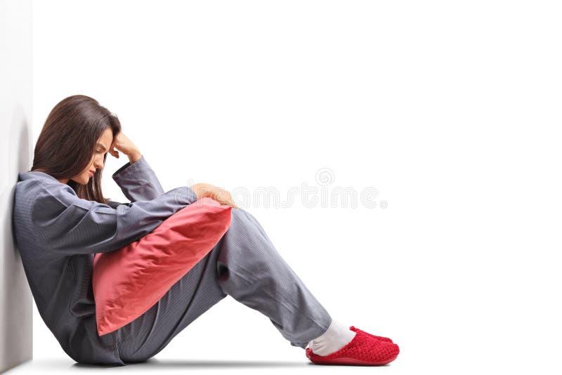 Droevige jonge vrouw in pyjama's die op de vloer zitten en pi houden royalty-vrije stock foto