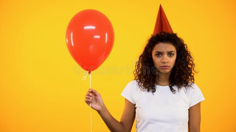 Droevige jonge vrouwelijke holdings rode ballon, die en eenzaam op verjaardagsviering wordt verstoord stock afbeelding