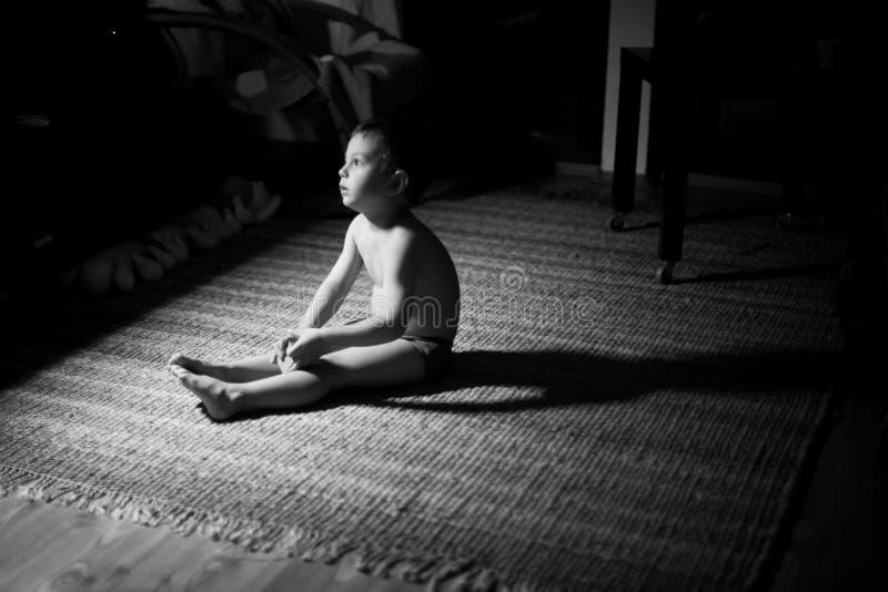 Droevige jongen in dark royalty-vrije stock afbeeldingen