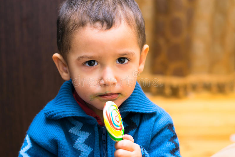 Droevige jongen die Lolly eten stock fotografie