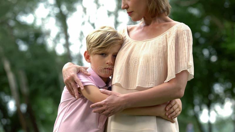 Droevige jongen die moeder, rouw koesteren van familielid, psychologisch trauma royalty-vrije stock afbeeldingen