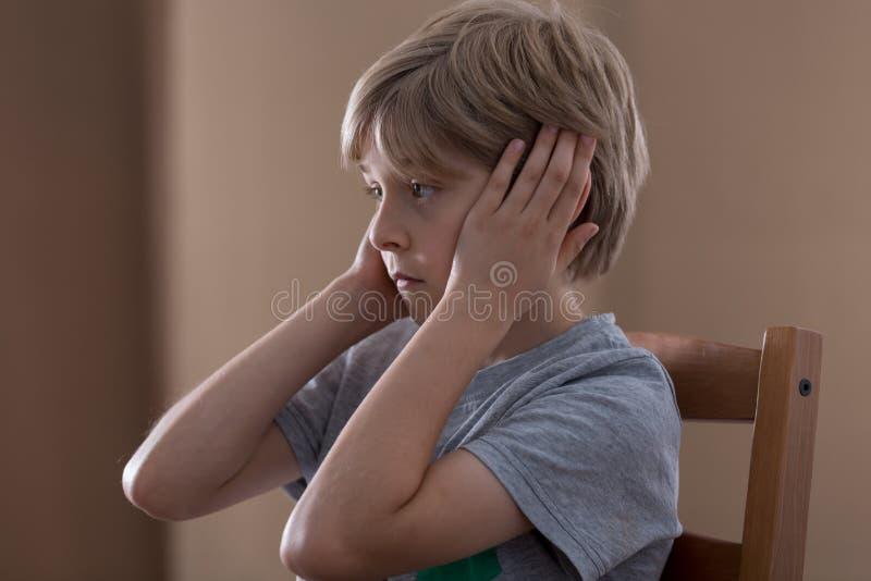 Droevige jongen die oren stoppen stock fotografie