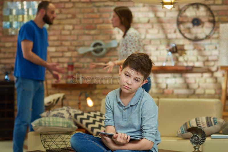 Droevige jongen die ouders stellen royalty-vrije stock foto