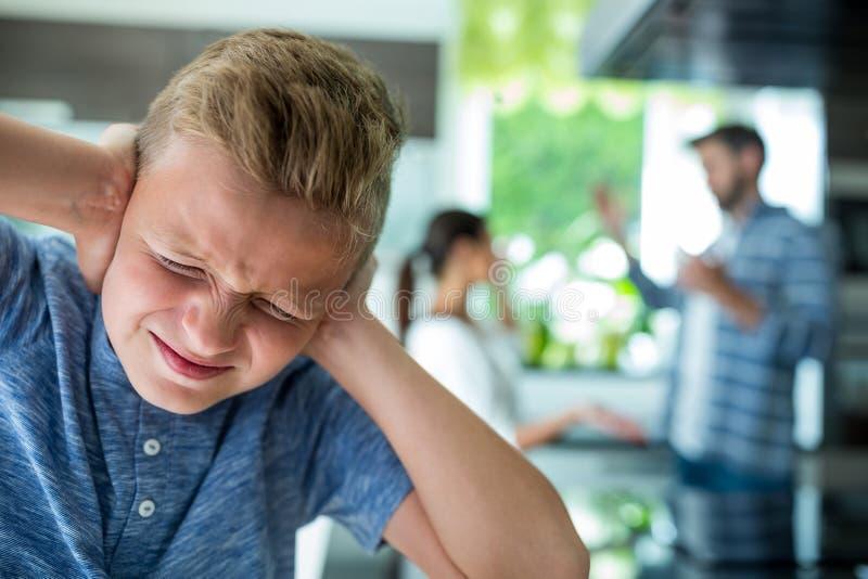 Droevige jongen die zijn oren behandelen terwijl ouders die op achtergrond debatteren royalty-vrije stock fotografie