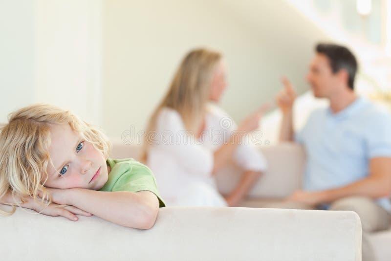 Droevige jongen met het stellen van ouders achter hem
