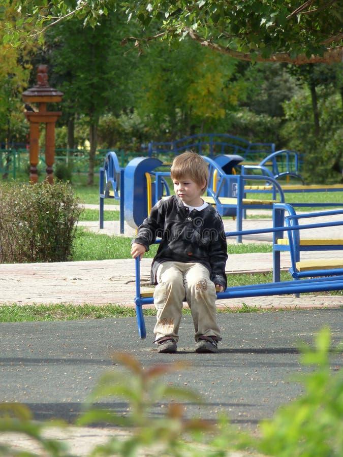 Droevige jongen op een parkbank. royalty-vrije stock afbeelding