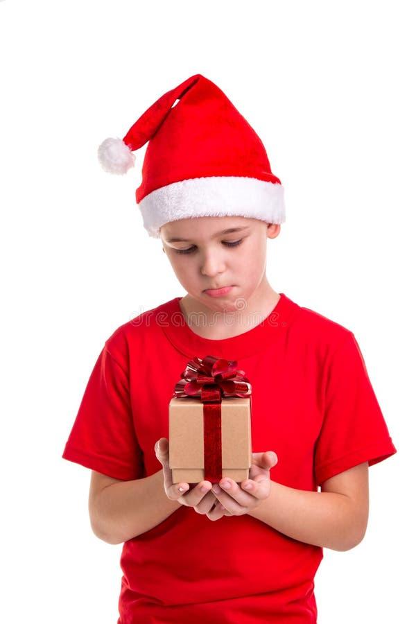 Droevige jongen, santahoed op zijn hoofd, met de kleine giftdoos in de handen Concept: Kerstmis of Gelukkige Nieuwjaarvakantie stock afbeeldingen