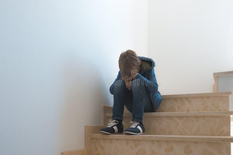Droevige jongenszitting alleen in de hoek in de trap stock foto