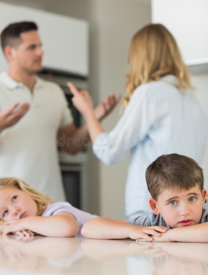 Droevige kinderen die op lijst leunen terwijl ouders het debatteren stock fotografie