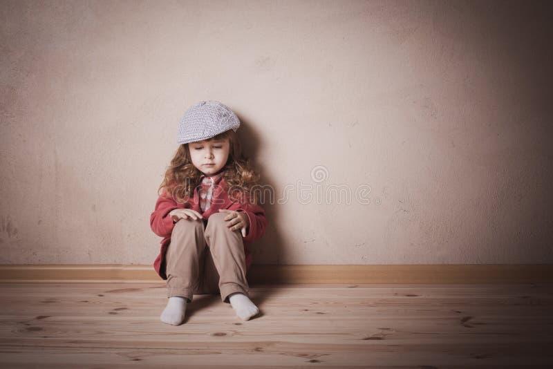 Droevige kindzitting op de vloer stock afbeeldingen