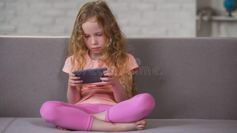 Droevige krullend-haired meisjeszitting op bank en het spelen op smartphone, verslaving stock afbeeldingen