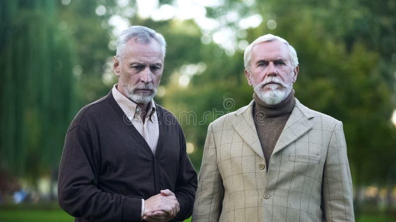 Droevige mannelijke gepensioneerden die verloren vriend in camera, oude, pensioneringsarmoede kijken royalty-vrije stock afbeelding