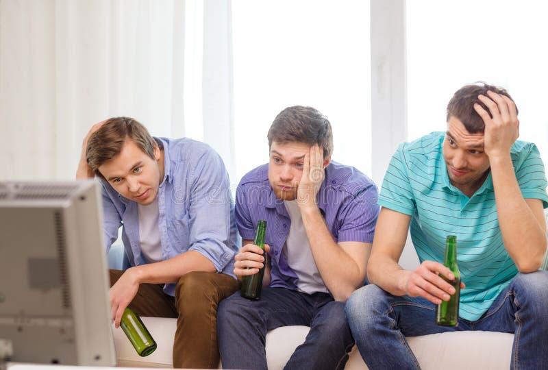Droevige mannelijke vrienden met bier het letten op sporten royalty-vrije stock afbeeldingen