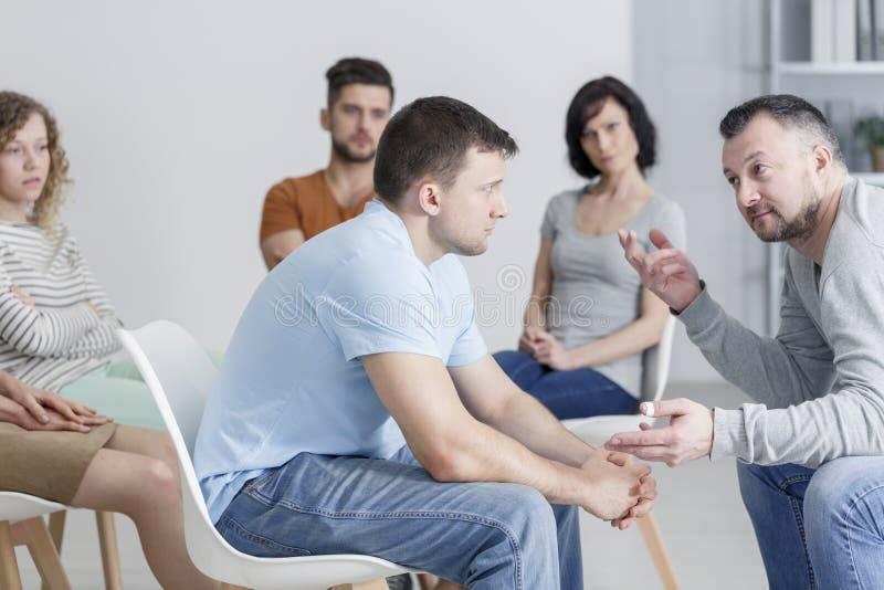 Droevige mens die aan therapeut luisteren stock afbeelding