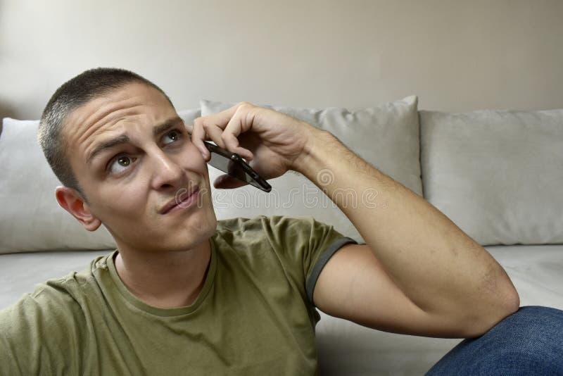 Droevige mens die mobiele telefoon in zijn handen houden stock fotografie