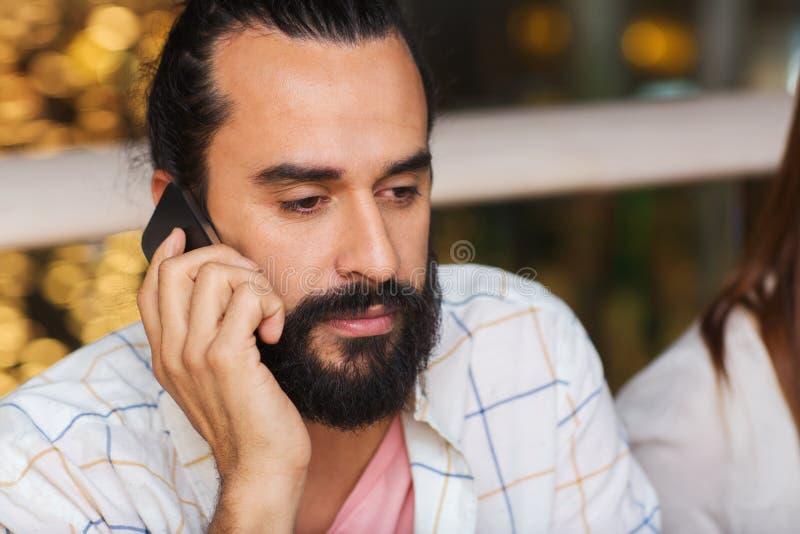 Droevige mens die smartphone uitnodigen bij restaurant stock afbeelding